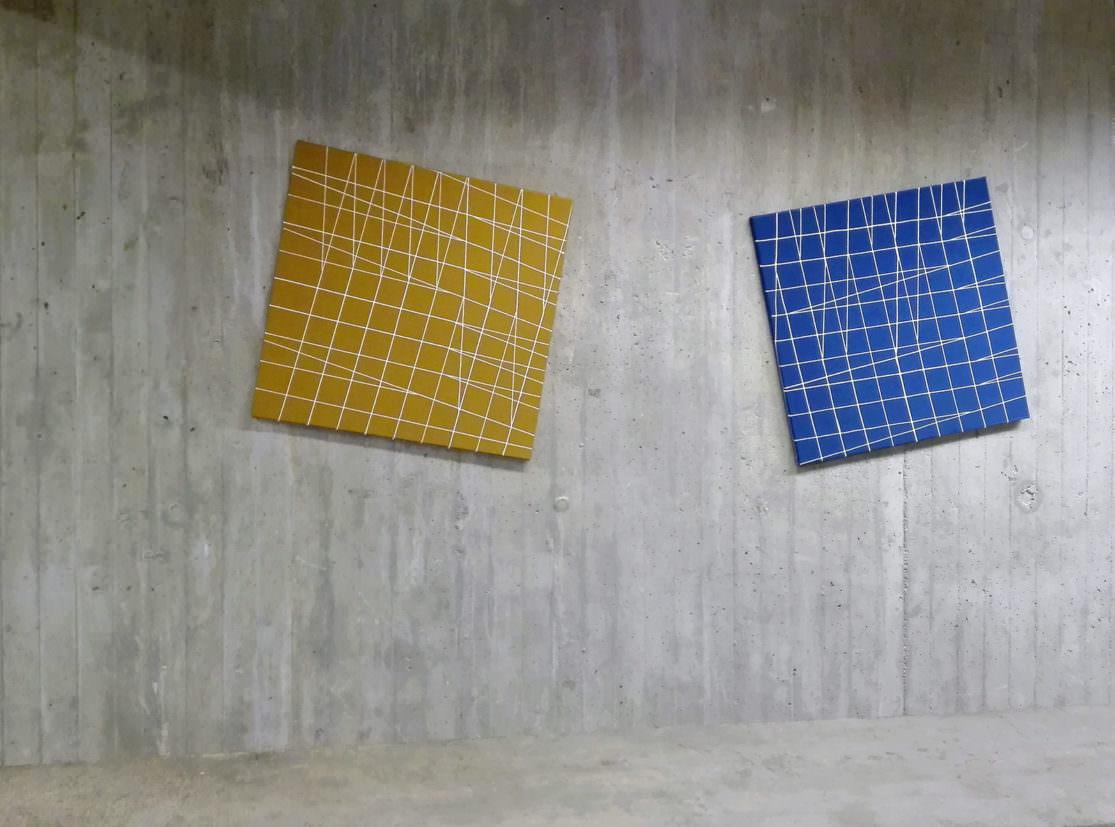ein dunkelgelbes und ein blaues quadratisches Bild, beiden mit weissen, sich kreuzenden LInien hängen in schiedfen Winkeln auf einer rohen Betonwand