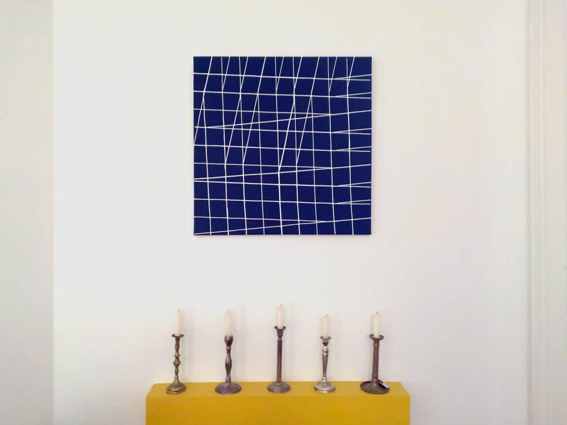 ein blaues Bild mit weissen schrägen Linien hängt an der Wn düber 5silbernen Kerzenleuchtern