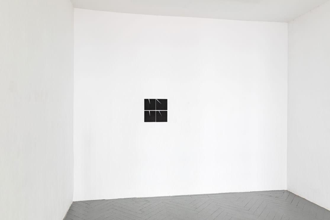 Weisse Wand mit skleinem schwarzen vierteiligen Bild