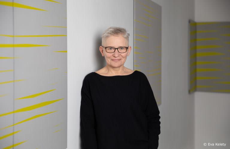 Halbportrait Barbara Höller an Wand lehenend mit Bildern mit gelben schmalen Rautenformen